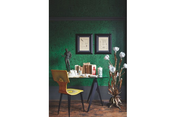 A yellow Fornasetti dining chair at a glass-topped writing desk against green malachite wallpaper