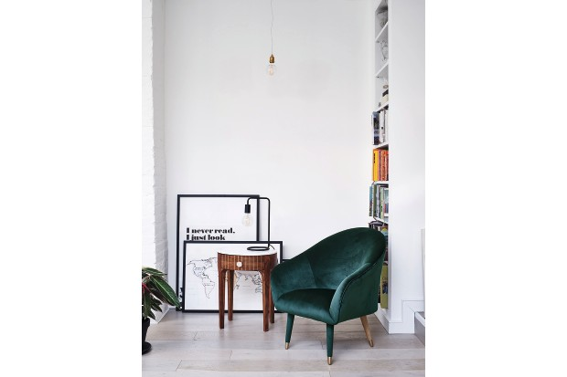 Contemporary typographic prints leant against a white wall beside a green velvet armchair