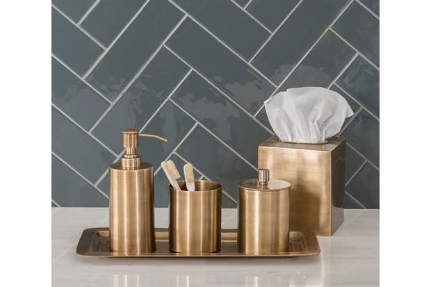 Green herringbone bathroom tiles behind a gold tray and soap dispenser