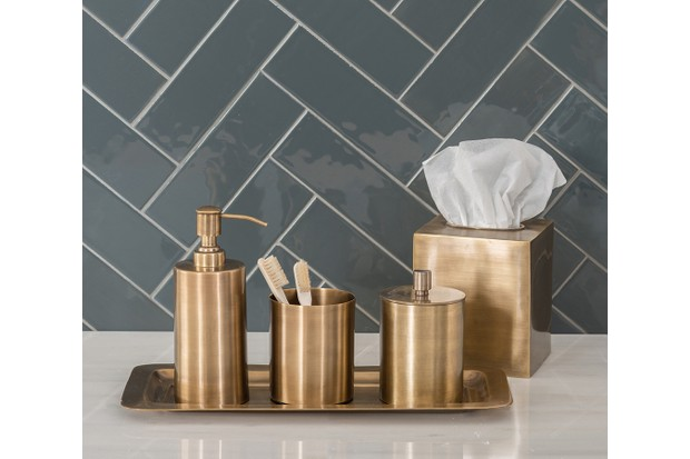 Green herringbone bathroom tiles behind a gold tray and soap dispenser