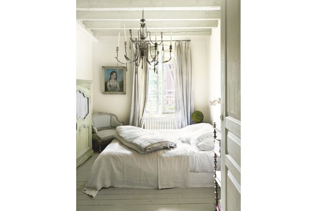 A grey French-style bedroom with a chandelier and distressed furniture