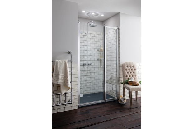 A glass shower enclosure with white metro tiles
