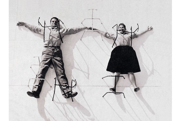 An archive photo of Charles and Ray Eames pinned to a white board with Eames Hang it Alls