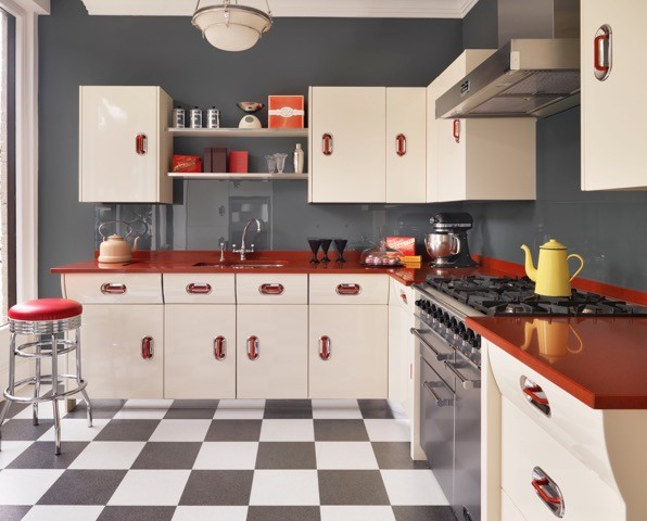 A kitchen with a gloss red quartz worktop and checkered floor