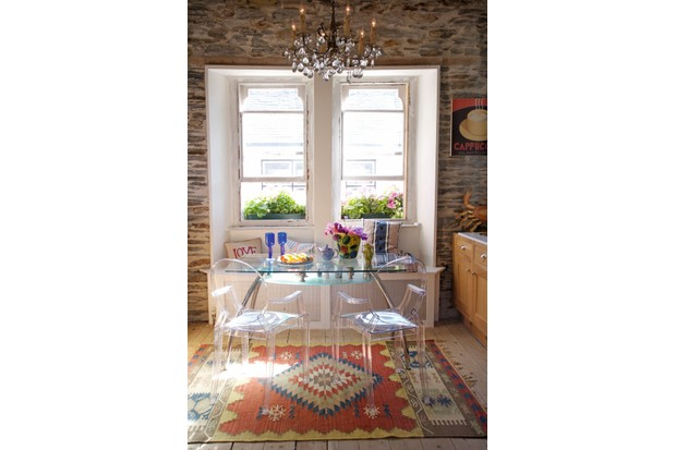 Lighted candle chandelier above glass topped table and pair of Philippe Starck chairs in country kitchen with Kelim rug