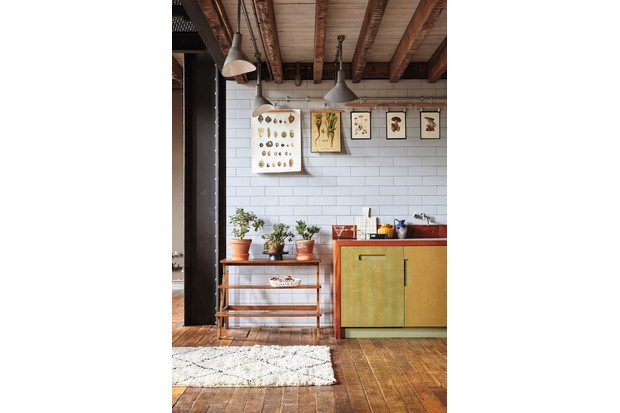 An industrial style kitchen with vintage botanical prints hanging in front of white metro tiles