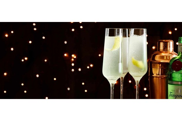 French 75 drinks in tall champagne flutes with lemon zest