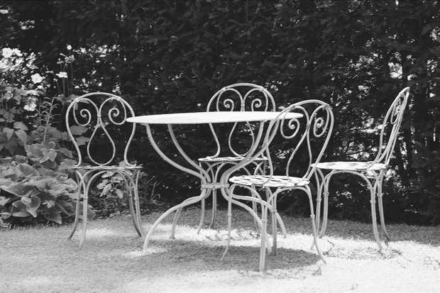 A white vintage metal garden set in a leafy garden