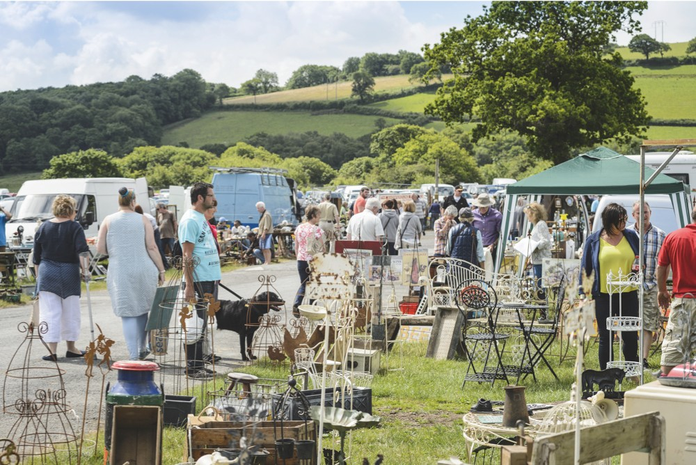 A crowd of people shopping for garden antiques at an antiques fair