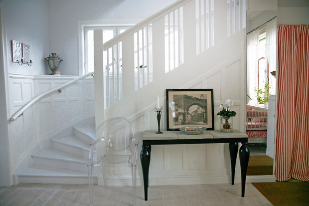 Philippe Starck Louis Ghost transparent chair next to side table in hallway with stairs
