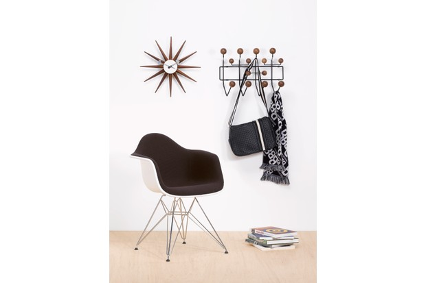 A special edition Eames Hang it All beside an Eames DSW armchair and a mid-century clock