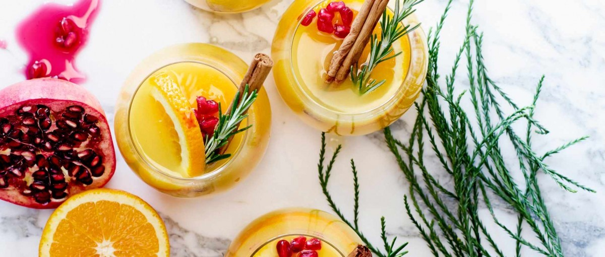 An aerial shot of orange cocktails with sprigs of rosemary and sticks of cinnamon