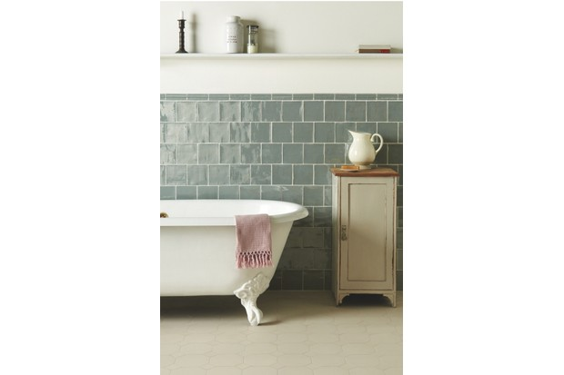 A white roll top bath with pale blue metro tiles