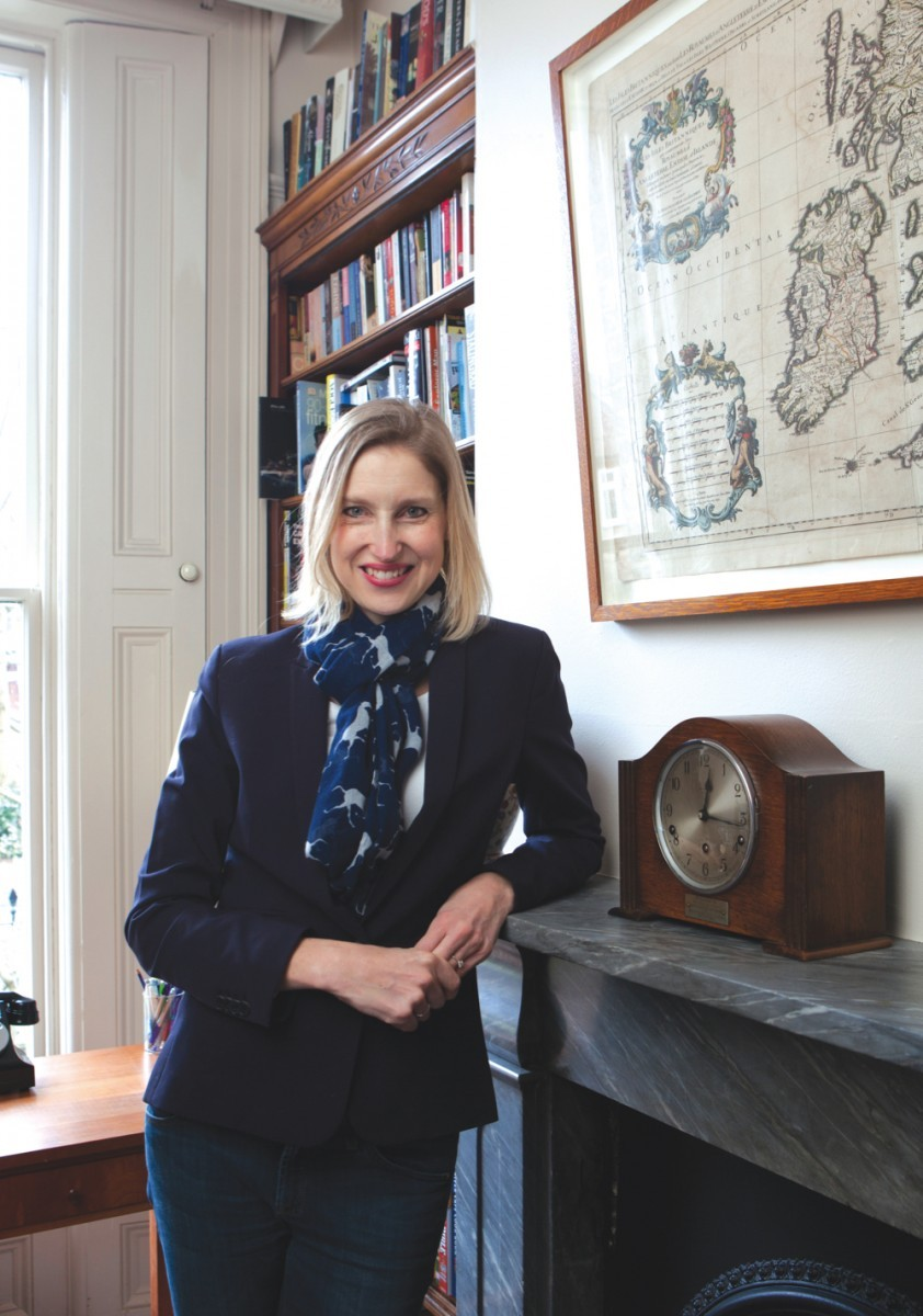A portrait of Tracy Borman beside her grandmother's antique mantel clock