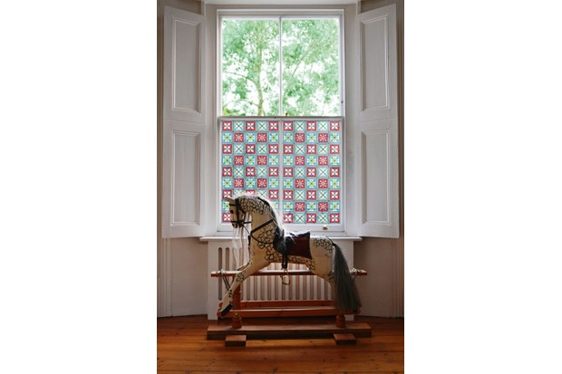 Victorian Stained Glass Film on a window behind an antique rocking horse