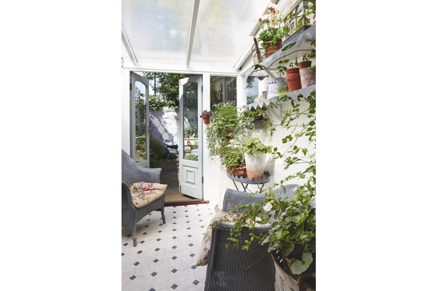 Two woven armchairs sit in the conservatory, which is filled with trailing plants