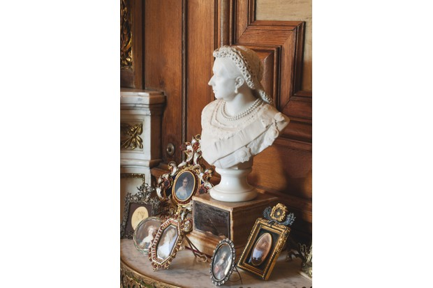 A marble sculpture of Queen Victoria sits between various small portraits