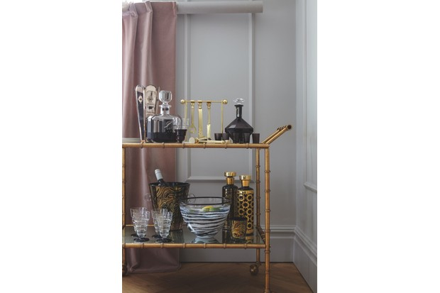 Vintage-style drinks trolley, £375, Out There Interiors. Curtain made in 'Quartz Velvet' in 'Rose' (ZREV331611), £107 per m, Zoffany. On drinks trolley: antique mirrored vase, £280, Alfies Antique Market. Palda or Posselt deco engraved and enamelled decanter, £325; Val St Lambert deco smokey plum decanter with shot glasses, £455, both Richard Hoppé. Barbell barware set, £198; 'Malachite' ice bucket, £198; 'Malachite' and 'Newport' decanters, £198 each; 'Malachite' glass, £25, all Jonathan Adler. 20th-century glass bowl vase, £120, Alfies Antique Market. Czechoslovakian stepped wine glasses, £480, Gazelles of Lyndhurst