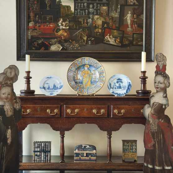 A pair of dummy boards either side of a Georgian console table displaying blue and white ceramics