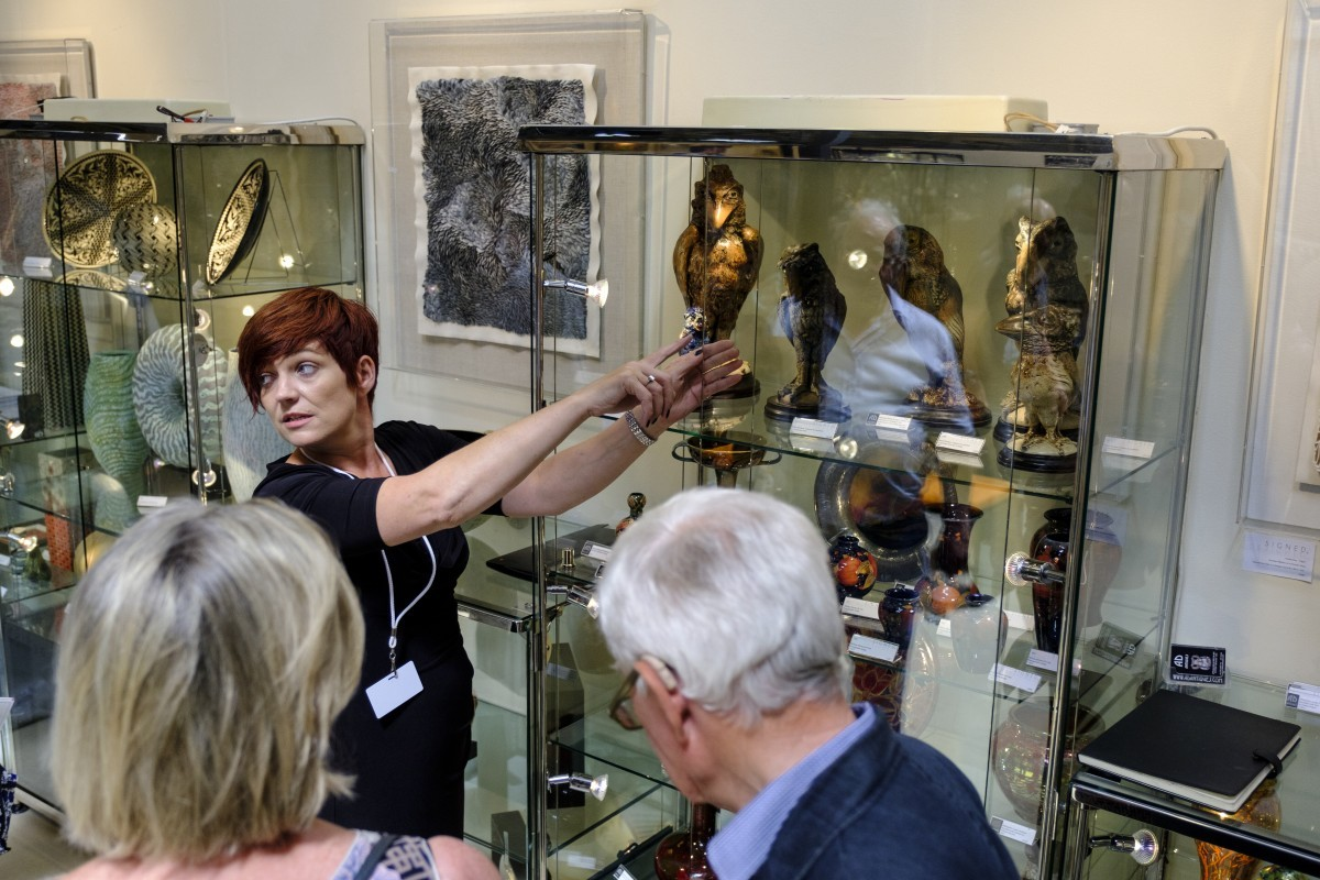 An antiques dealer pointing at a glass display case full of Martin Brothers birds