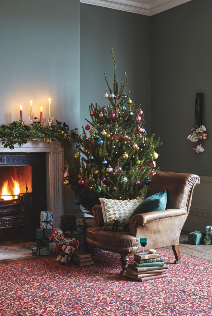 A vintage brown leather armchair beside a roaring fire and twinkling Christmas tree
