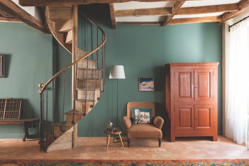 A wooden spiral staircase stands adjacent to an armchair and a wooden cupboard