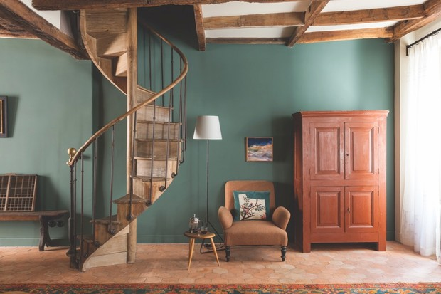An antique armchair and spiral staircase in a small living room