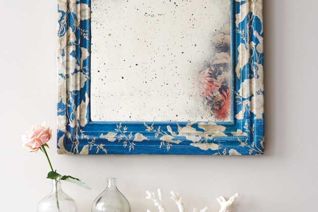 A mirror framed with a blue and white flower pattern