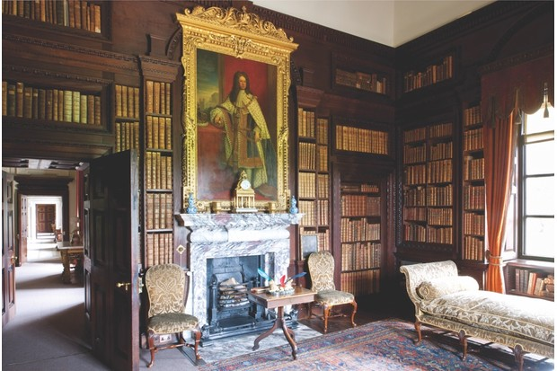 The library of Houghton Hall. A portrait of King George I in a baroque frame is the focus of this room