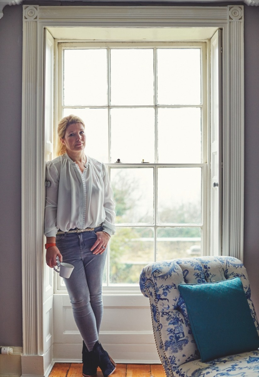 Lizzie Gordon standing in front of a window inside her home