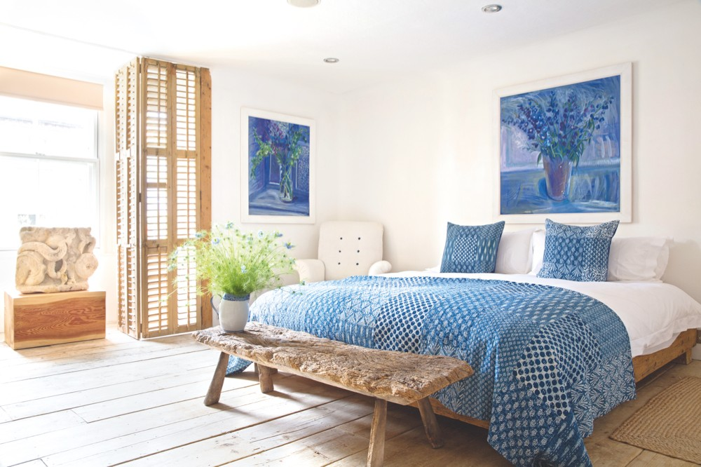 Picture of master bedroom with two paintings by Pauline Liu-Devereux