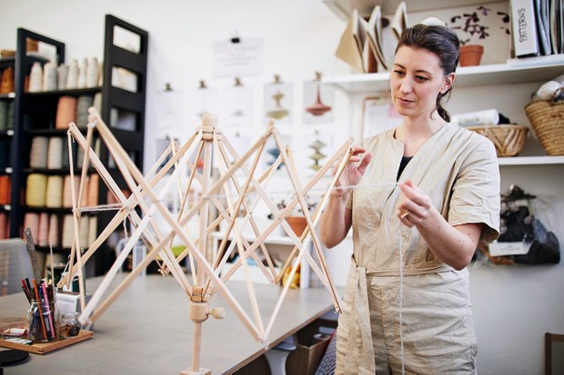 Naomi begins twisting yarn around a wooden frame to create a lampshade