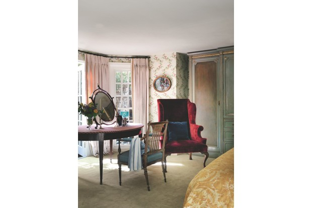 A small bedroom with an antique dressing table, mirror and red velvet armchair