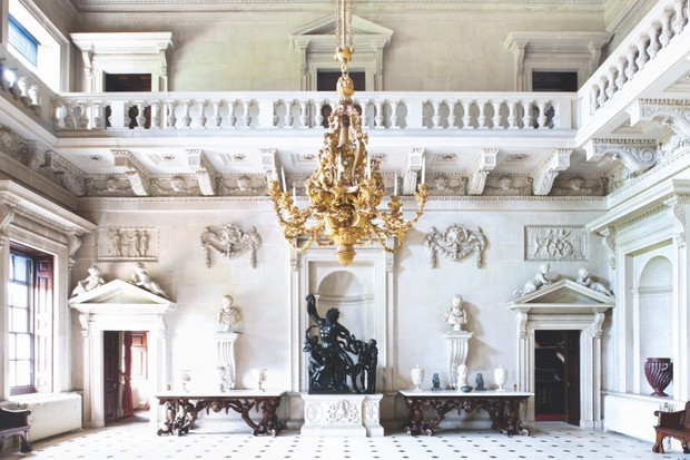 The stone hall of Houghton Hall. A chandelier hangs from the centre of the room