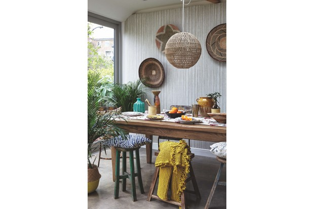A room with an antique dining table and woven straw baskets on the wall