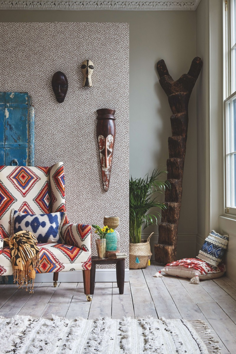 An Ikat-print armchair against a wall hanging with tribal masks