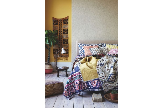 A tribal style quilted bedspread rests on a double bed