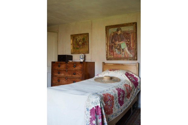 A wooden chest of drawers is next to a single bed with a straw hat on it