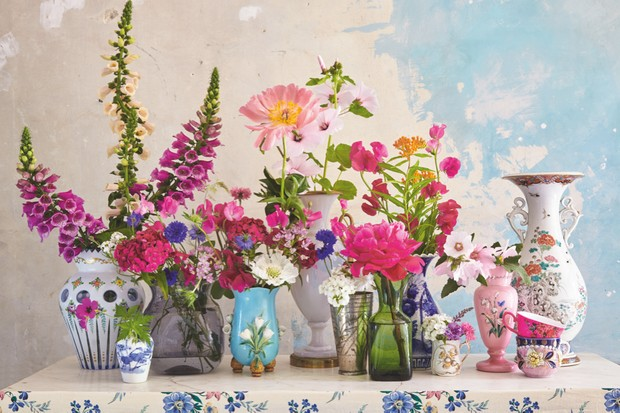 An array of antique glass vases filled with summer flowers