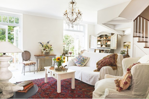 More french windows in the living room are accompanied by a chandelier in the centre of the room, and a white sofa and armchair