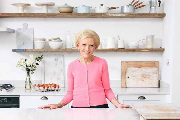 A portrait of Mary Berry in a pink cardigan in front of open shelves filled with cake tins and ceramics