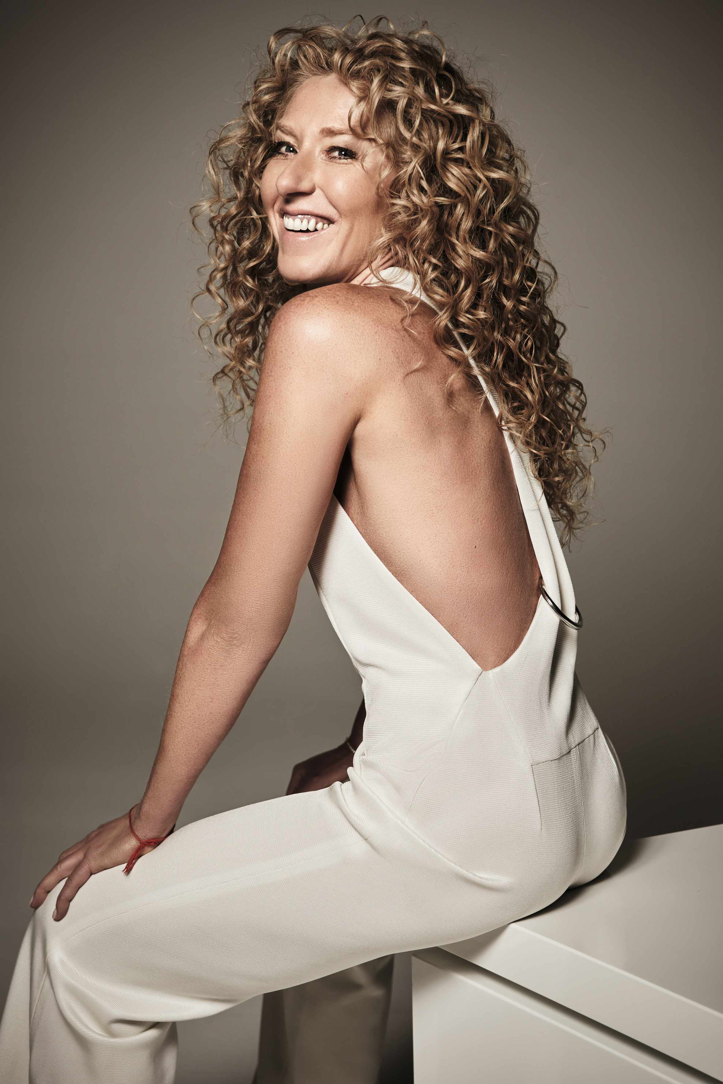 A portrait of Kelly Hoppen in a white jumpsuit