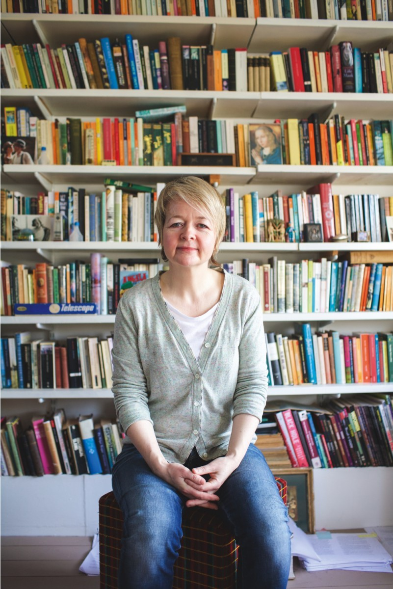 Novelist Sarah Waters sitting in front of a bookshelf
