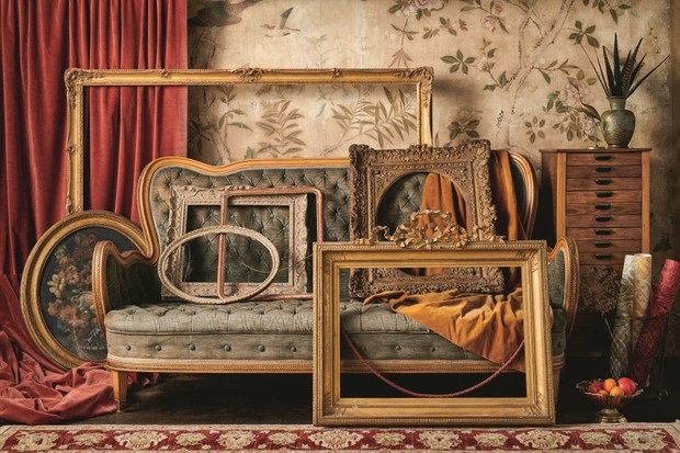Antique gilded frames in different sizes and shapes leant against an antique sofa.