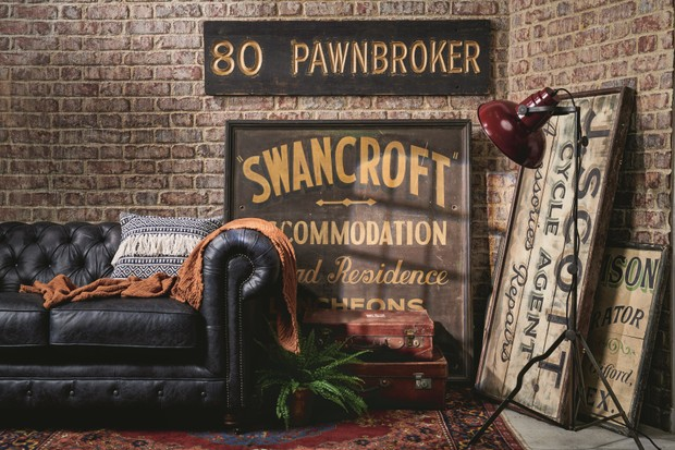 An array of vintage signs leant against an exposed brick wall alongside black leather Chesterfield sofa.