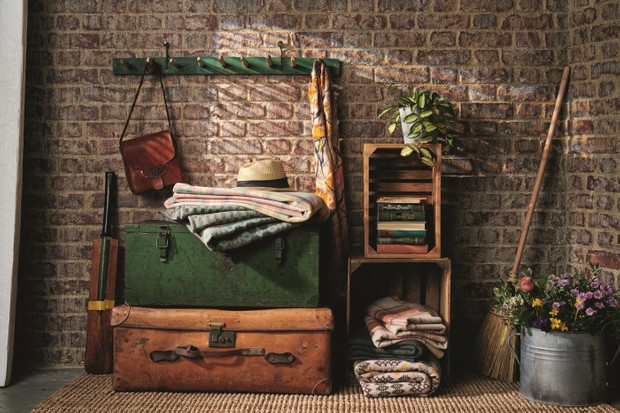An exposed brick hallway with hooks and antique trunks used to store winter coats and blankets