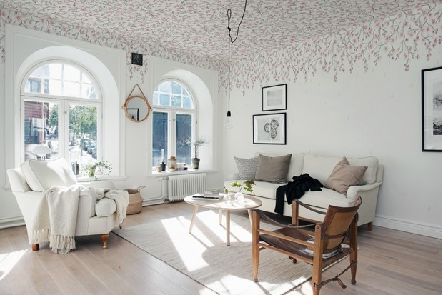 Floral wallpaper used on the ceiling in a large, white room