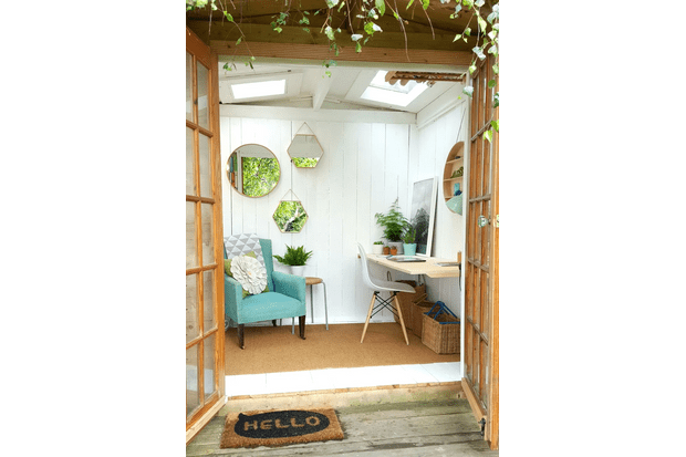 An outdoor office space filled with a teal armchair and a cluster of hexagonal mirrors on the wall