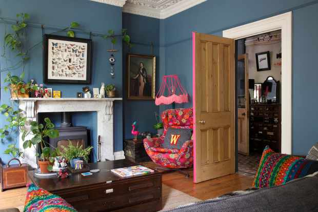 Helen Ward's deep blue living room featuring a wood burner, pops of neon and a reupholstered Egg chair