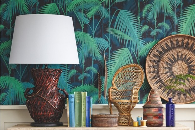 A console table stacked with a vintage lamp and miniature peacock chair beside palm-print wallpaper
